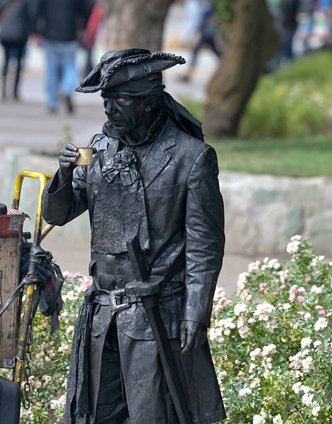 Pirate Street Performer taking a yerba mate break Coyhaique, Chile – February 16, 2016: a street performer takes a mate break in the Pentagonal Plaza of Coyhaique, the capital city of both the Coyhaique province and Aysen Region, Chile.  The pirate holds in his right hand the traditional mate cup with metal straw.   michael stephen wills south america stock pictures, royalty-free photos & images