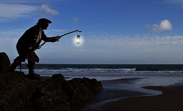 pirate with lantern standing on rocks at beach - swashbuckler stock photos and pictures
