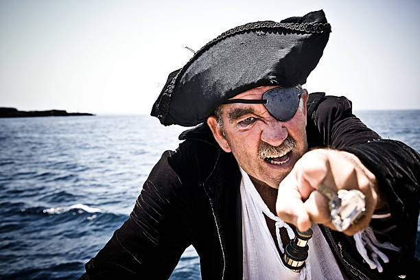 pirate with sea background pointing at camera very aggressive - pirates stock photos and pictures