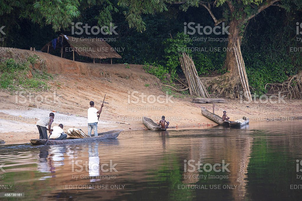 Pirogue (dugout canoe) approaching small village at Congo River royalty-free stock photo
