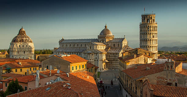 Pisa Rooftops A view of Pisa's Cathedral Square, featuring the Cathedral, the Tower and the Baptistery, taken just after sunrise. pisa stock pictures, royalty-free photos & images