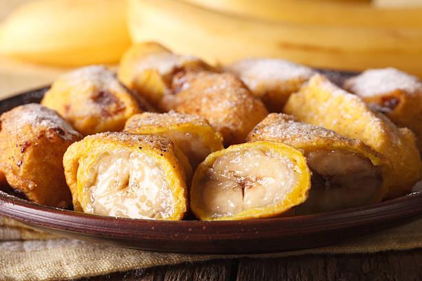 Pisang goreng fried bananas in batter on plate macro. Horizontal - foto de acervo