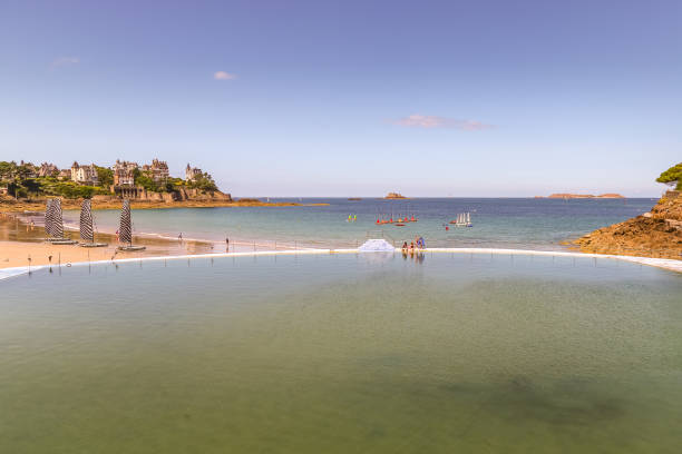 Piscine de mer pool, people sit on the waters edge at lowtide with a view directly across the harbour. stock photo