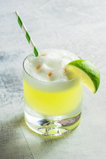 Pisco Sour Cocktail in Glass with Lime and Straw A pisco sour in a rocks glass with a straw, garnished with a lime wedge. This cocktail is made from Peruvian pisco liquor, lime juice, simple syrup, and egg white shaken together and topped with a couple dashes of bitters. pisco peru stock pictures, royalty-free photos & images