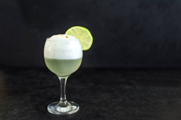 Pisco Sour Cocktail Pisco Sour Cocktail. Peruvian, Mexican, Chilean traditional drink pisco sour liqueur with  lime and egg on black background. pisco peru stock pictures, royalty-free photos & images