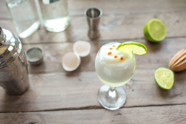 Pisco Sour Cocktail Pisco Sour Cocktail. Peruvian, Mexican, Chilean traditional drink pisco sour liqueur with  lime and egg and bar equipment for making. pisco peru stock pictures, royalty-free photos & images