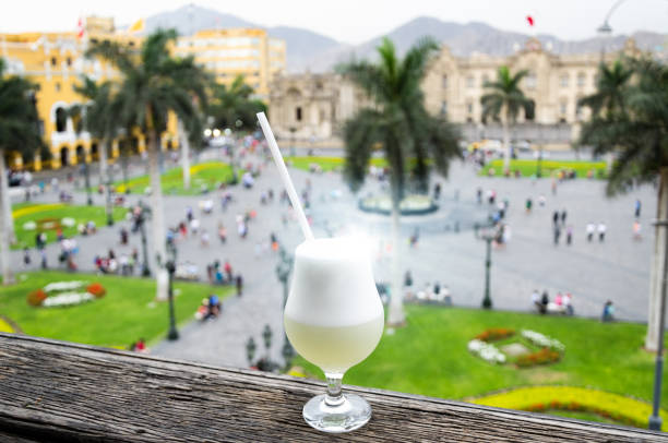 Pisco sour homemade cocktail with the background of the main square of Lima Pisco sour homemade cocktail with the background of the main square of Lima - Peru pisco peru stock pictures, royalty-free photos & images