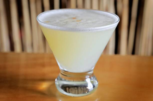 Pisco Sour Peruvian traditional drink Pisco Sour traditional Peruvian drink on a wooden table with cane bottom pisco peru stock pictures, royalty-free photos & images