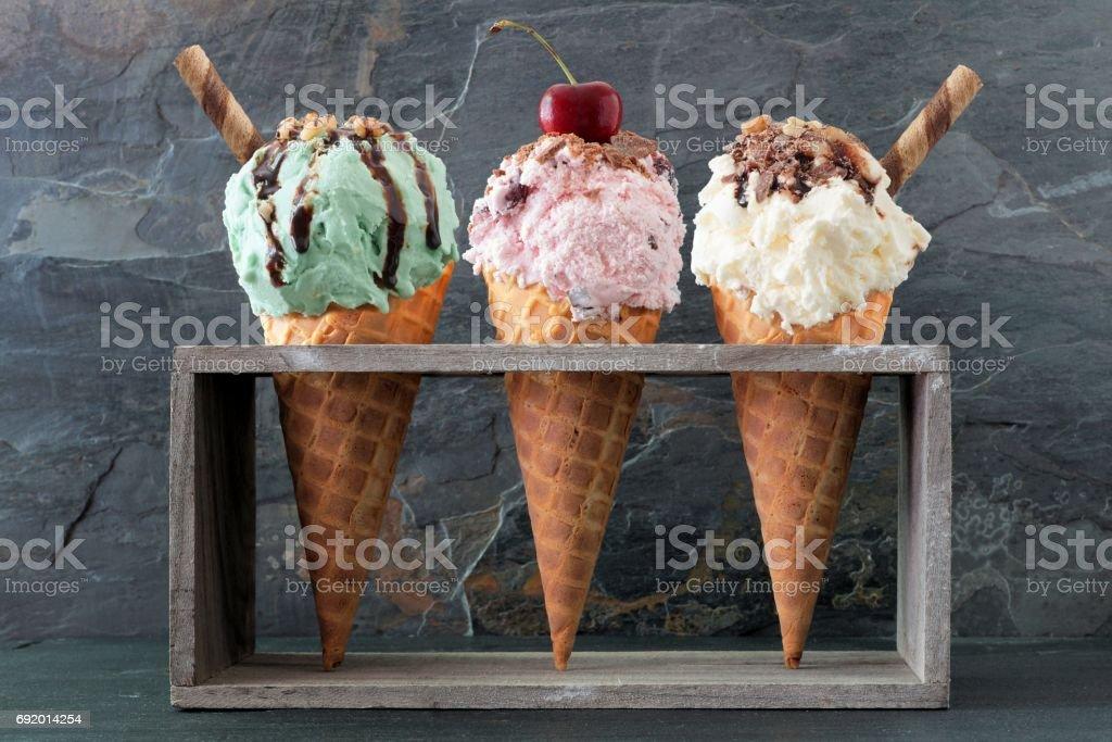 Pistachio, cherry and vanilla ice cream in waffle cones over slate stock photo