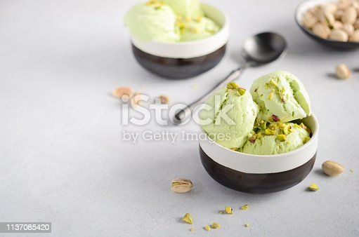 Pistachio ice cream in a bowls on a gray concrete background, selective focus.