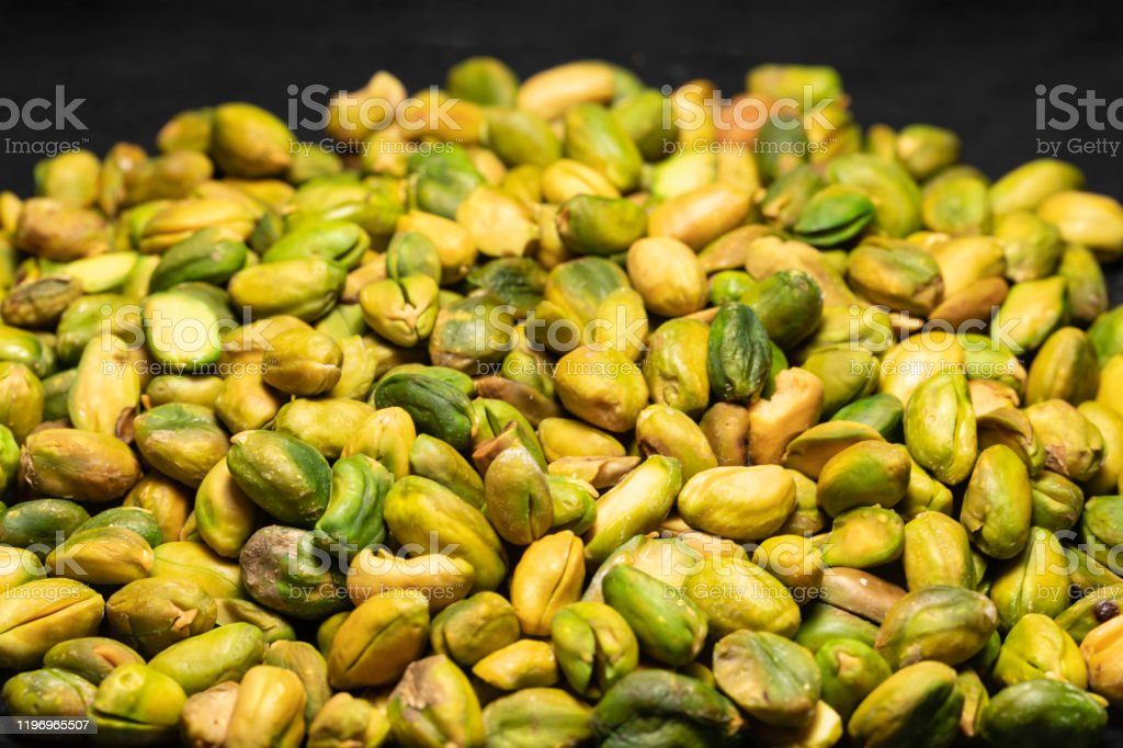 pistachio in heap Pistachio is a dry fruit produced by a shrub of Mediterranean climate, the true pistachio of the Anacardiaceae family. It is in the form of a small seed of greenish color and sweet flavor, housed in a shell which opens when the fruit is ripe. Bean Stock Photo