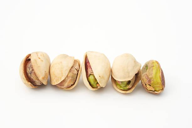 pistachio nut in a line peeled shell stock photo