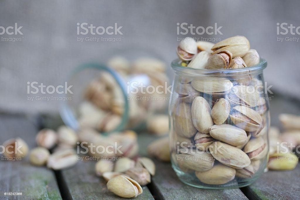 Pistachio nuts in a glass bottle stock photo