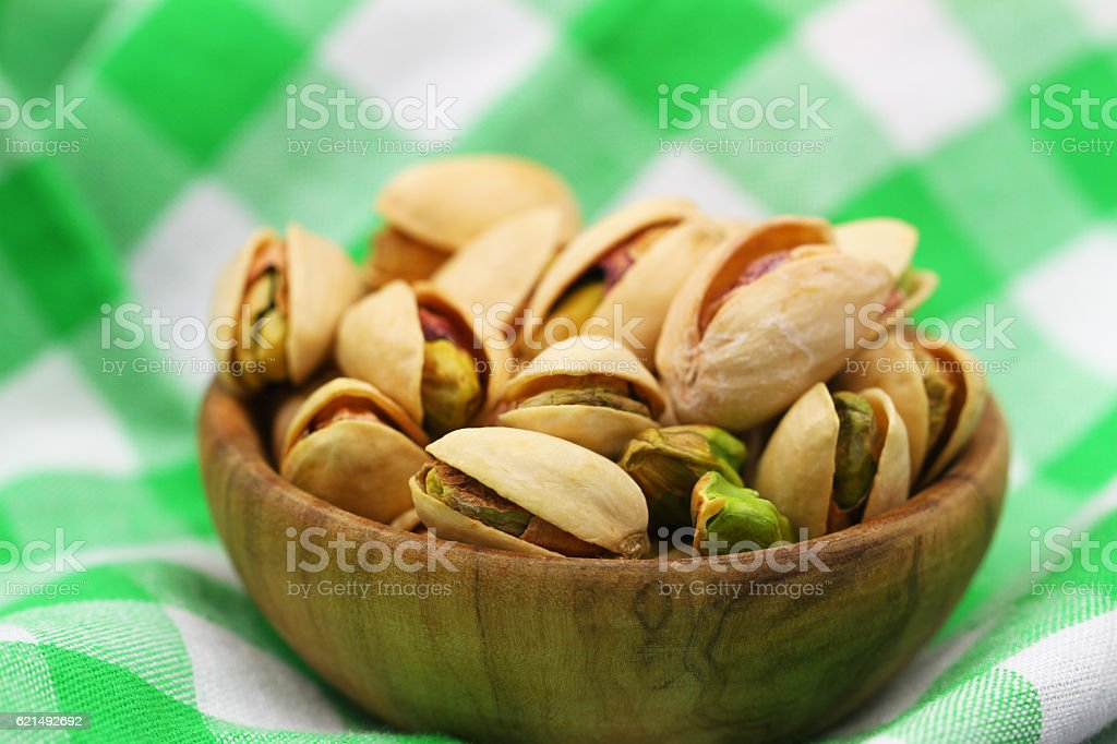 Pistachio nuts in wooden bowl on checkered cloth, closeup foto stock royalty-free