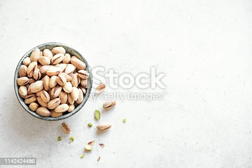 Pistachio nuts. Green salted pistachios in ceramic bowl on white background, copy space, top view.