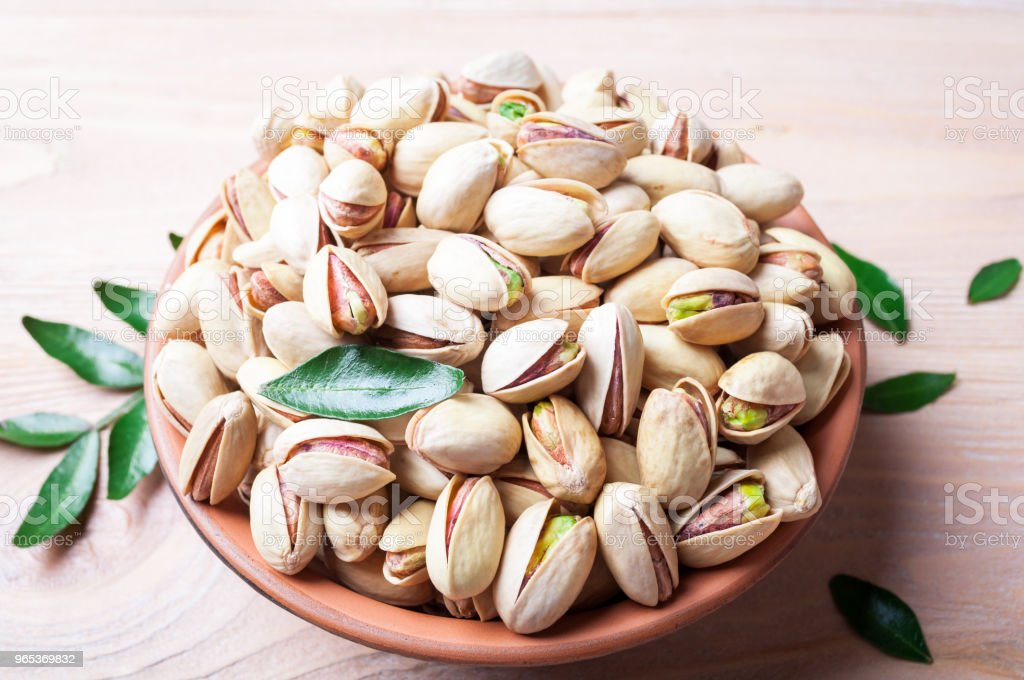 Pistachios nuts in bowl. Pistachio with leaves. Healthy food, snacks, vegetarian zbiór zdjęć royalty-free