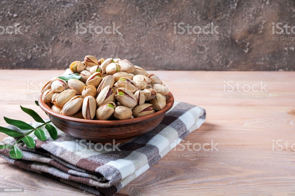Pistachios nuts in bowl. Pistachio with leaves. Healthy food, snacks, vegetarian food zbiór zdjęć royalty-free
