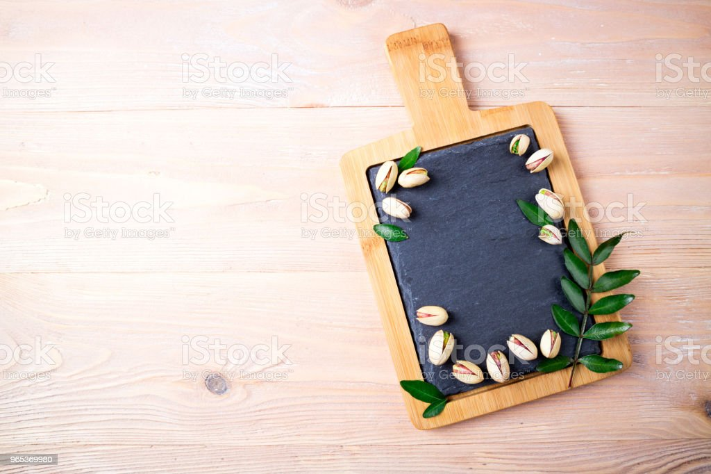 Pistachios nuts on stone board. Pistachio with leaves. Healthy food, snacks, vegetarian food. Top view zbiór zdjęć royalty-free