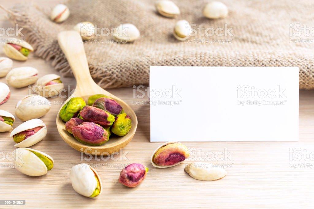 Noix pistaches avec une cuillère en bois et papier blanc simulé vers le haut sur le fond de la table en bois. Mise en page créative avec la notion de caractère avec un espace pour le texte. - Photo de Aliment libre de droits