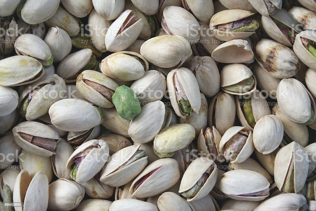 Pistachios with a single wasabi pea royalty-free stock photo