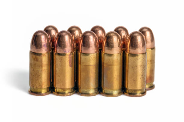 Pistol Bullets in Line Ten pistol bullets in line isolated on white background. deathly stock pictures, royalty-free photos & images