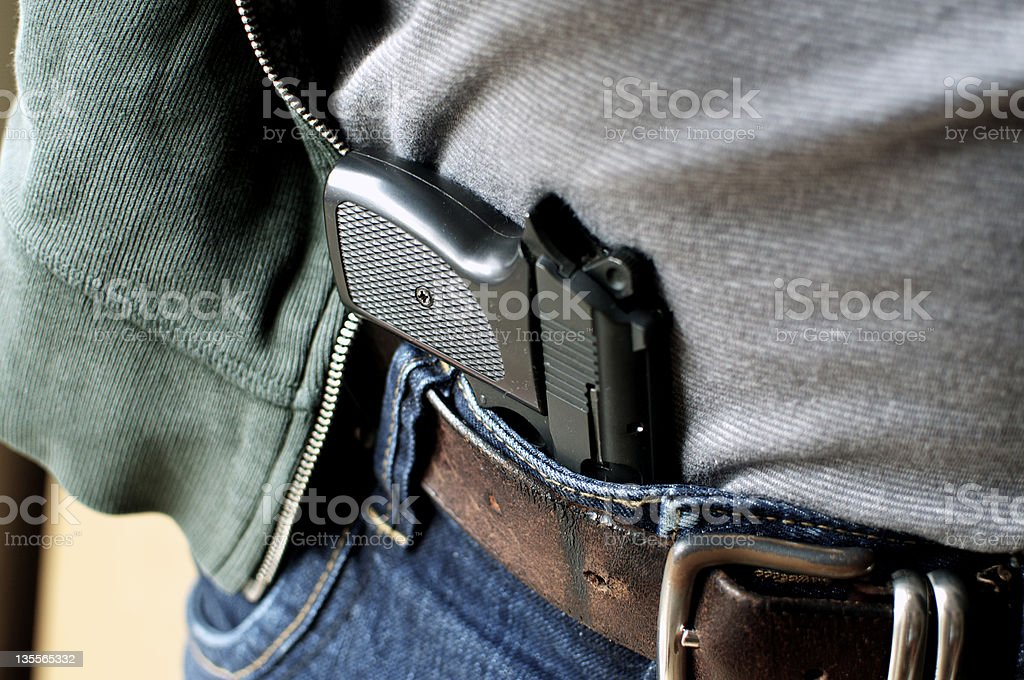 Pistol hidden in belt stock photo