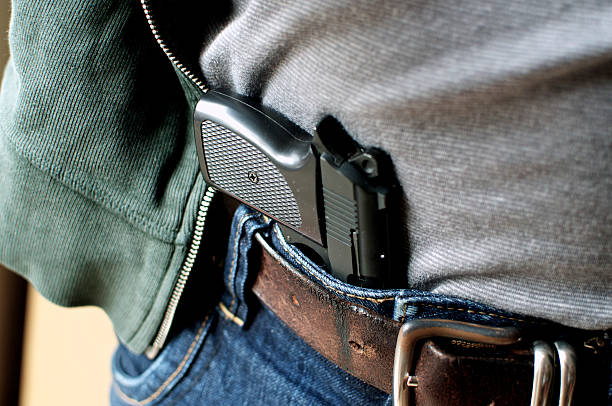 Pistol hidden in belt Tucked in a belt pistol being concealed pistol stock pictures, royalty-free photos & images