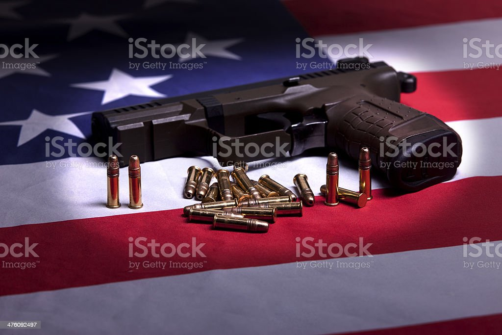 Pistol on flag in the spotlight. stock photo