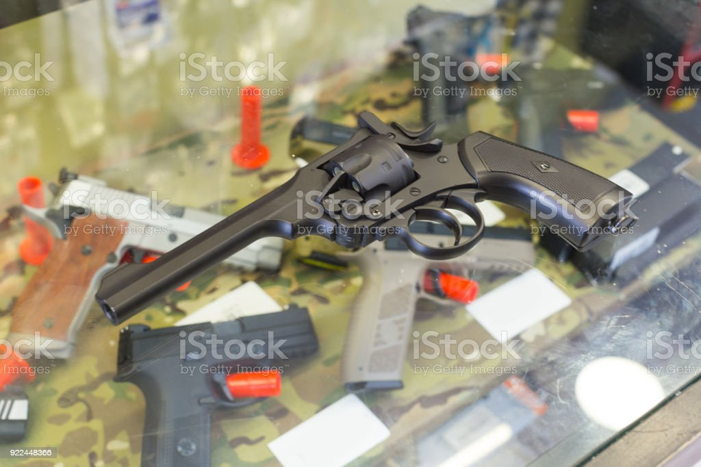 pistol on the glass table in army shop stock photo
