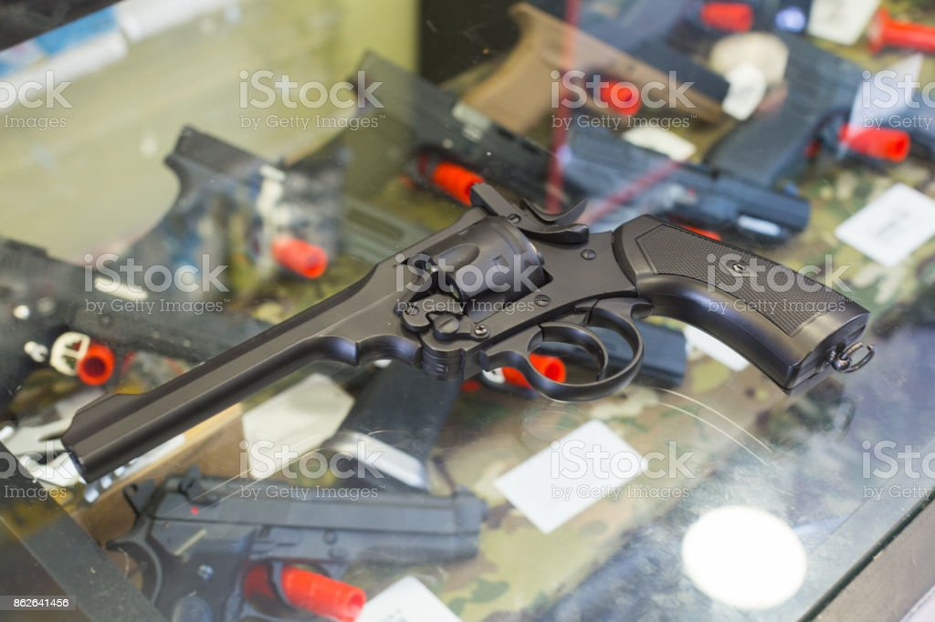 pistol on the glass table in military store stock photo