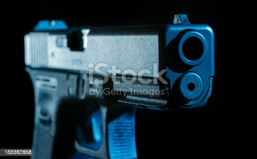 A close look at the barrel of a 9mm semi automatic pistol in hard studio light. Cold steel with a touch of blue.