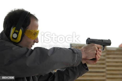 Man shooting for practice with fitted goggles and headphones for noise.