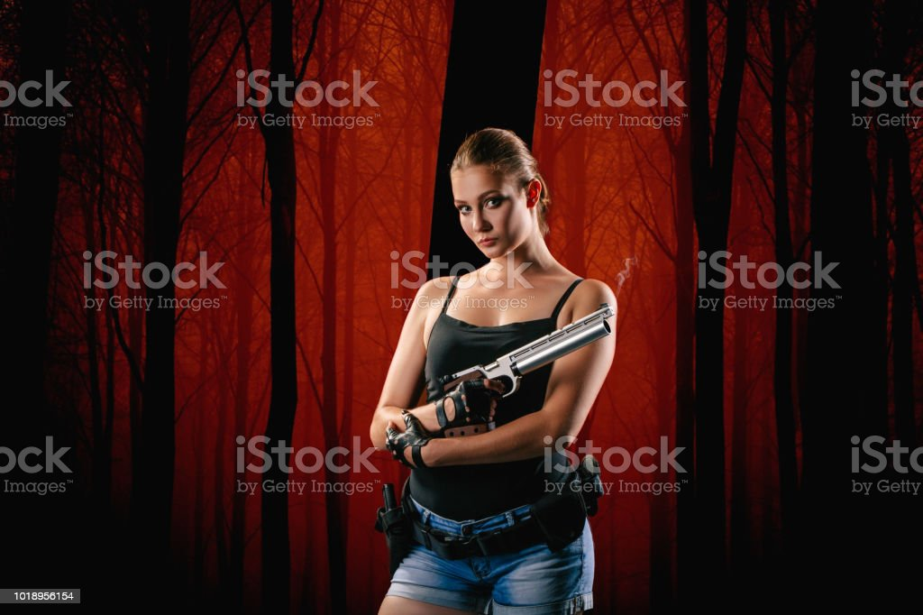 Pistol shooting isolated on red forest background. Sportsman with a gun. Sport pistol shooting. stock photo