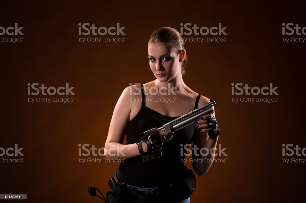 Pistol shooting on dark red background. Sportsman with a gun. Sport pistol shooting. stock photo
