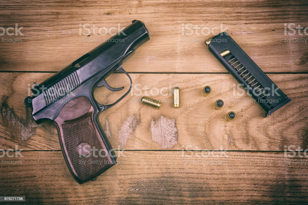 Pistol with bullets and cartridge on the wooden surface, set stock photo