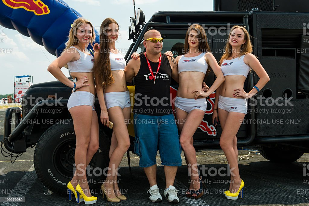 Pit girls and racer pose before the races stock photo