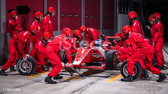 istock Pit stop team working on a red formula race car 1126023902