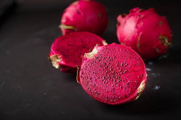 pitaya cut in half, auf schwarzem hintergrund - kaktusfrucht stock-fotos und bilder