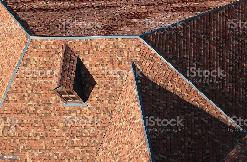 Pitched tiled shingle roof with attic window stock photo
