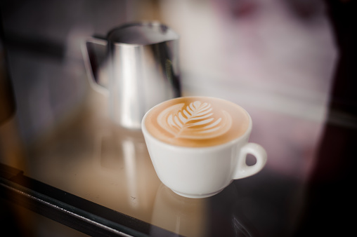 istock Pitcher and coffee cup with beautiful latte art on the table 915770306