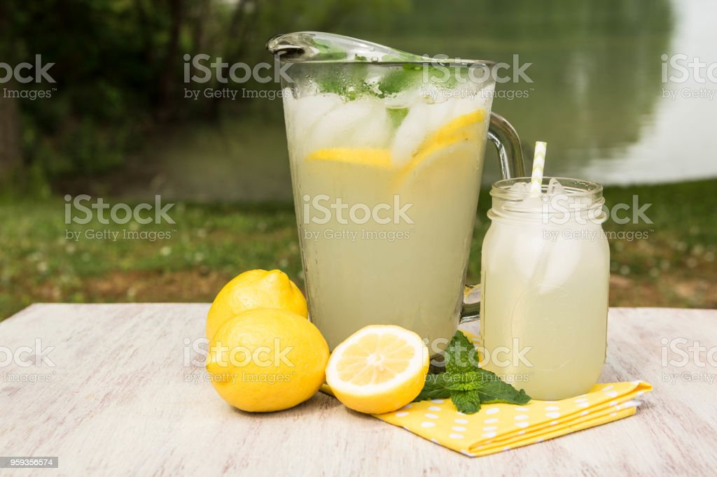 Pitcher and Glass of Lemonade By The Lake stock photo