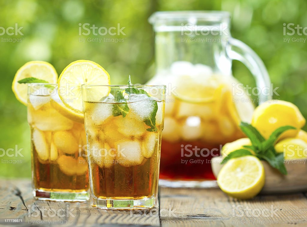 Pitcher and glasses of iced tea with lemons stock photo