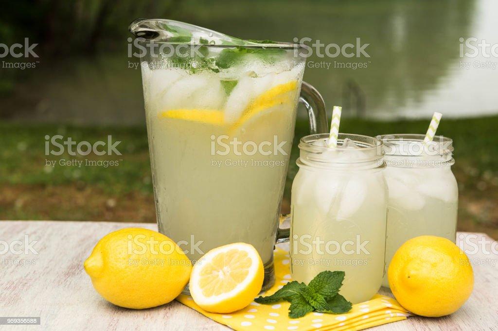 Pitcher and Mugs of Lemonade Outside By Lake stock photo