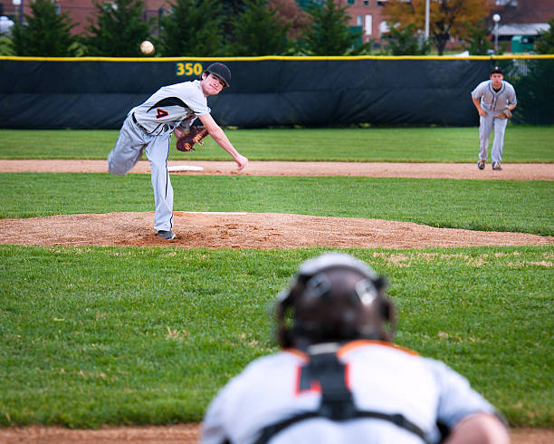 Pitcher following through pitching motion, ball in mid-air stock photo