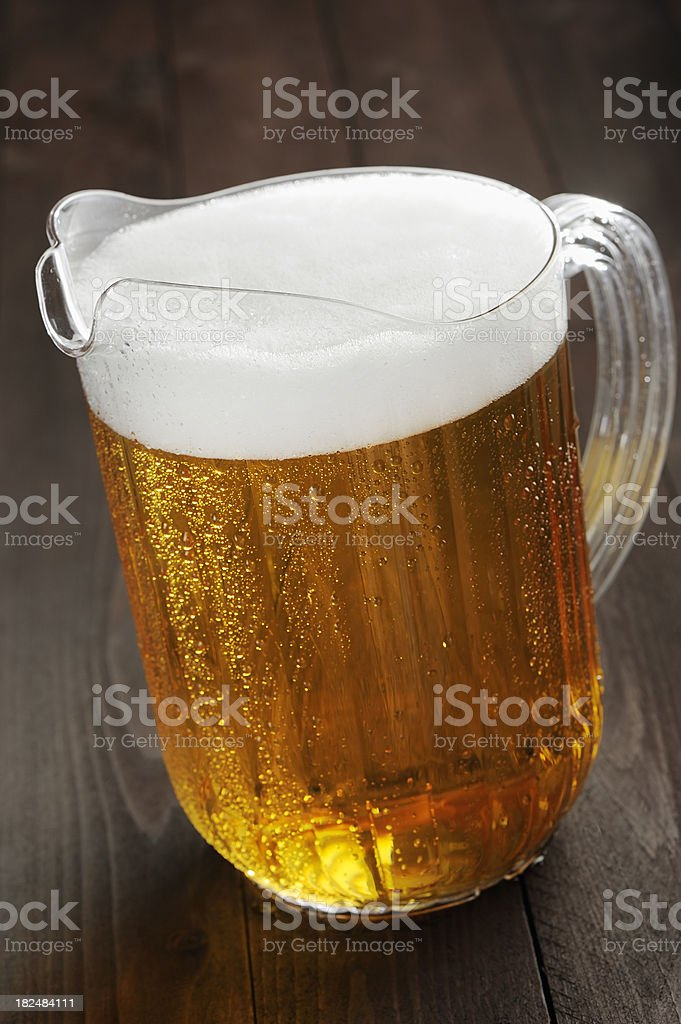 Pitcher of foamy beer on a wooden table stock photo