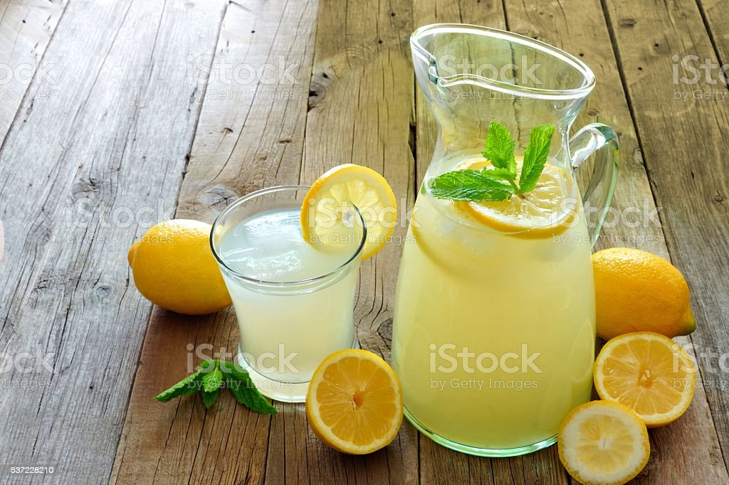 Pitcher of fresh lemonade with filled glass on wooden stock photo