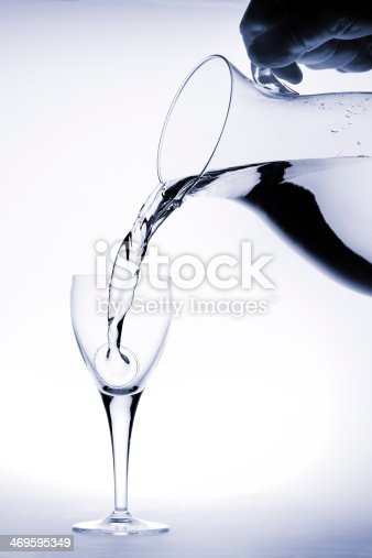 629189244istockphoto Pitcher pours water into a glass 469595349