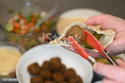 Person filling pitta bread with falafel ball and Middle Eastern salads.