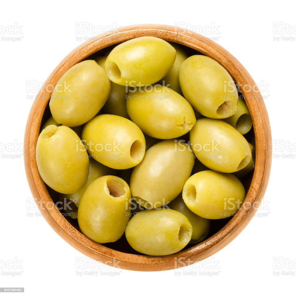 Pitted and marinated green olives in wooden bowl stock photo