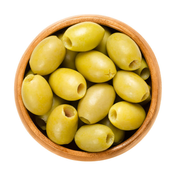 Pitted and marinated green olives in wooden bowl Pitted and marinated green olives in wooden bowl. Fruits of the European olive, Olea europaea. Unripe table olives with yellow to green color. Isolated macro food photo close up from above over white. olives stock pictures, royalty-free photos & images